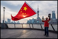 Man saluting Chinese flag and skyline, the Bund. Shanghai, China ( color)