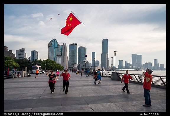 Joggers salute Chinese flag flown on kite line, the Bund. Shanghai, China (color)