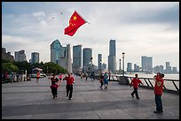 Joggers salute Chinese flag flown on kite line, the Bund. Shanghai, China ( color)