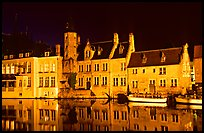 Houses reflected in canal, Rozenhoedkaai, night. Bruges, Belgium