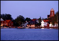 Houses, church, across the lake at dusk, Vadstena. Gotaland, Sweden