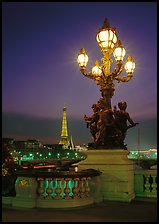 Bronze lamp post with scultpure on Pont Alexandre III, and Eiffel Tower at night. Paris, France ( color)