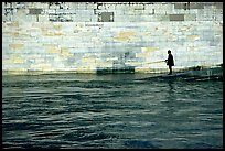 Man standing at water level fishing in the Seine River. Paris, France ( color)