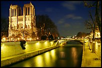Facade of Notre Dame and Seine river at night. Paris, France