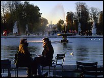 Couple sitting by basin in Tuileries Gardens. Paris, France