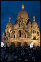 Tourists sitting on the stairs of the Sacre coeur basilic in Montmartre at night. Paris, France (color)