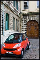 Tiny car on coblestone pavement in front of historic house. Lyon, France