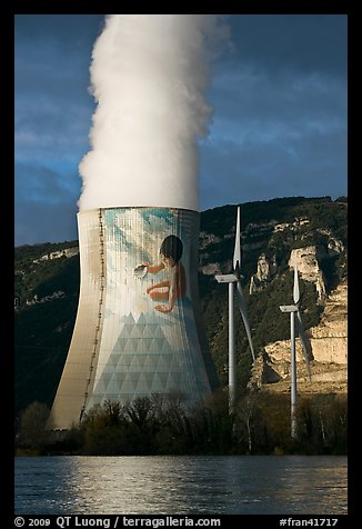 Cooling tower of nuclear power plant with ecology-themed art by Jean-Marie Pierret, and windmill. Provence, France
