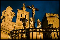 Cross with Christ, statues, and towers, evening light. Avignon, Provence, France