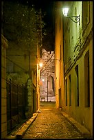 Narrow street leading to Palais des Papes at night. Avignon, Provence, France