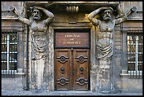 Wooden door framed by sculptures. Aix-en-Provence, France ( color)