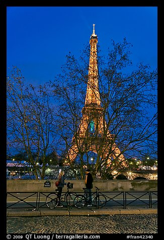 Bicyclists and Eiffel tower at night. Paris, France