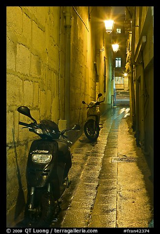 Motorcycles parked in narrow alley at night. Quartier Latin, Paris, France