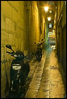 Motorcycles parked in narrow alley at night. Quartier Latin, Paris, France ( color)