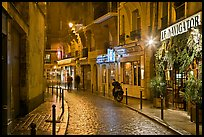 Street with cobblestone pavement and restaurants by night. Quartier Latin, Paris, France