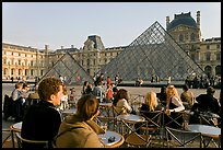 Cafe terrace in the Louvre main courtyard with glass pyramid. Paris, France