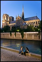 Two women having picnic across Notre Dame cathedral. Paris, France