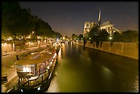 Quay, lighted boats, Seine River and Notre Dame at night. Paris, France