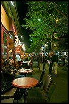 Couple walking by outdoor tables of cafe at night. Paris, France