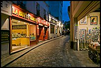 Narrow cobblestone street and businesses at night, Montmartre. Paris, France