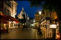 Place du Tertre at night with restaurants and Basilique du Sacre-Coeur, Montmartre. Paris, France