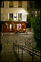 Hillside stairs on butte, street and restaurant at night, Montmartre. Paris, France