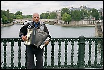 Street musician playing accordeon on River Seine bridge. Paris, France ( color)