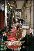 Couple eating at an outdoor table in the Palais Royal arcades. Paris, France