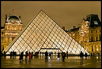 People standing in front of Louvre Pyramid by night. Paris, France ( color)