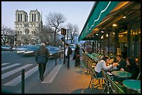 Cafe, street, and Notre Dame at dusk. Quartier Latin, Paris, France