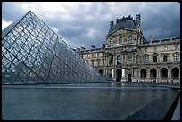 Pyramid and Richelieu wing of the Louvre under dark clouds. Paris, France