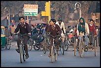Children riding bikes in rickshaws on way to school. New Delhi, India (color)