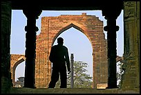 Man at entrance of ruined Quwwat-ul-Islam mosque. New Delhi, India