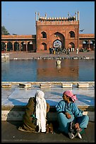 Women sitting near basin in courtyard of Jama Masjid. New Delhi, India