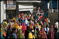 Street with women in colorful sari following wedding procession. Jodhpur, Rajasthan, India