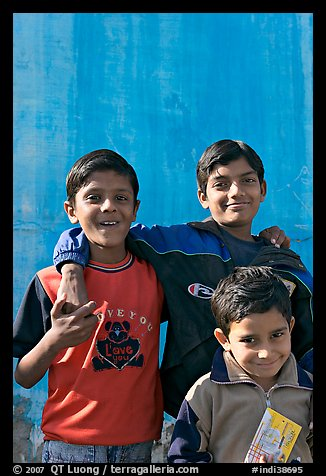 Young boys in front of blue wall. Jodhpur, Rajasthan, India