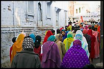 Women in colorful sari walking a  narrow street during wedding. Jodhpur, Rajasthan, India