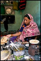 Woman with headscarf stacking chapati bread. Jodhpur, Rajasthan, India
