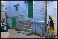 Woman walking in narrow street with blue walls. Jodhpur, Rajasthan, India