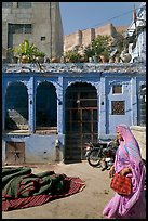 Woman in sari, blue house, and fort in the distance. Jodhpur, Rajasthan, India