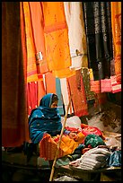 Woman selling fabrics at night. Varanasi, Uttar Pradesh, India