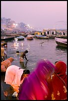Women on the banks of the Ganga River in rosy dawn light. Varanasi, Uttar Pradesh, India