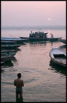 Man standing in Ganga River and boats at sunrise. Varanasi, Uttar Pradesh, India (color)