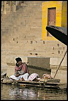 Man sitting near unbrella. Varanasi, Uttar Pradesh, India
