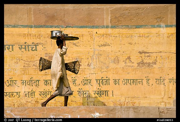 Man carrying a plater in front of wall with inscriptions in Hindi. Varanasi, Uttar Pradesh, India