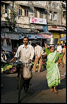 Man riding bike and woman with basket on head, Colaba Market. Mumbai, Maharashtra, India