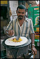 Man preparing breakfast dosa, Colaba Market. Mumbai, Maharashtra, India