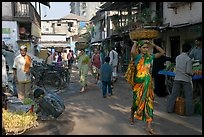 Women carrying  baskets on head in narrow street, Colaba Market. Mumbai, Maharashtra, India ( color)