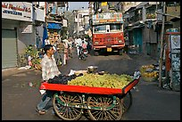 Vegetable vendor pushing cart with truck in background, Colaba Market. Mumbai, Maharashtra, India ( color)