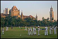 Boys in cricket attire on Oval Maidan, High Court, and Rajabai Tower. Mumbai, Maharashtra, India ( color)